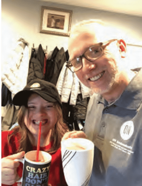 Steve Willison and grandaughter cheers to the camera smiling holding hot chocolate mugs