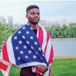 young african american man wearing a flag draped across his shoulders standing outside with lake in background looking pensive