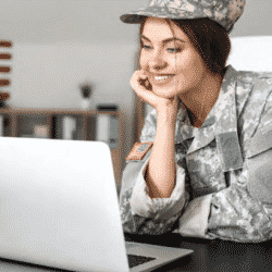 woman in military uniform seated at computer desk looking at screen smiling with flags in the background