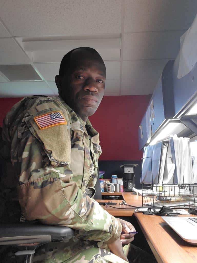 Army Spc. Immanuel Gitamo in uniform seated at his desk looking towards the camera over his right shoulder