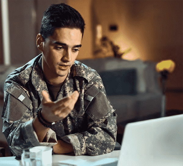 man dressed in fatigues sitting at a desk on a remote interview