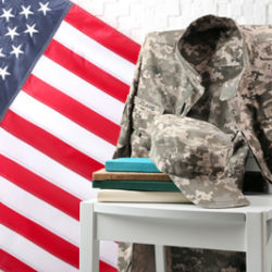 Chair, books, soldier uniform and USA flag near light textured wall