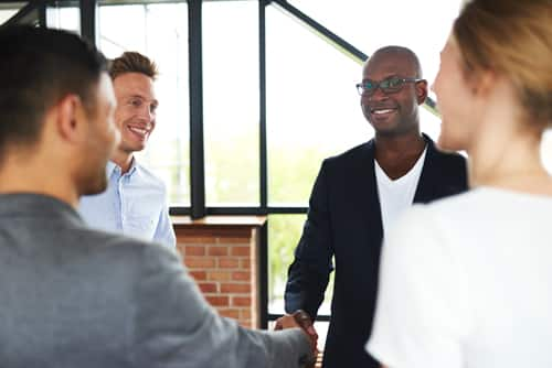 Black man and white man smiling and shaking hands while standing with colleagues