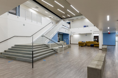 The inside of the Innovations Academy with an open staircase and visiting room downstairs