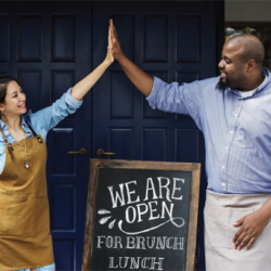 former service members now businessman and business woman high five each other outside their cafe