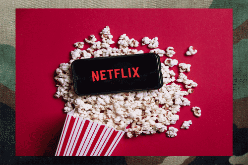 netflix on smartphone sitting on a bucket of popcorn with a camouflage background