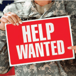 veteran in fatigues holding up sign that says help wanted