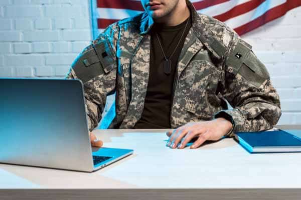 cropped view of soldier in uniform using laptop in office