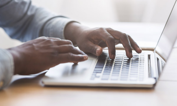 unrecognizable african american man typing on laptop keyboard