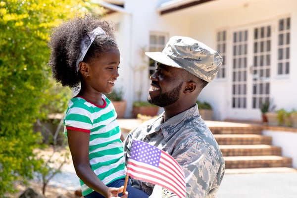 African American male soldier holding his daughter with a US flag