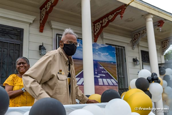 LAwrence Brooks stands on porch with balloons