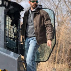 Patrick Montgomery outdoors standing on large farming vehicle looking over property