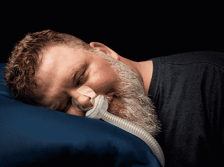man lying down on pillow with breathing device attached to nose