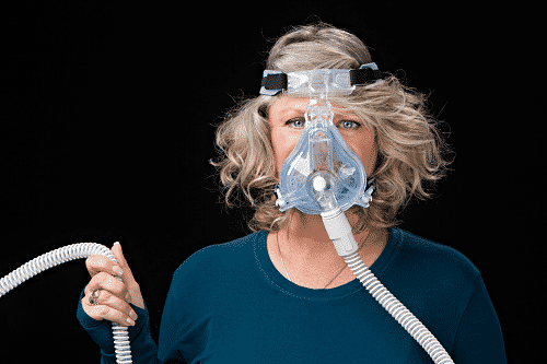 women holding up attached large breathing device
