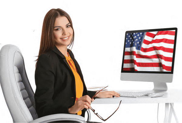 young military spouse sitting behind desk with laptop and flag in background