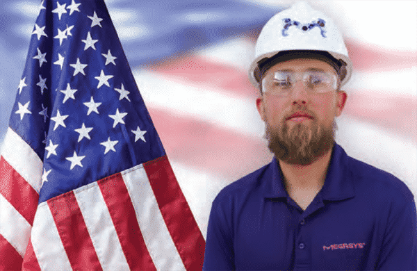 man with blue work shirt and cap standing next to american flag