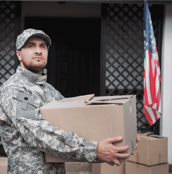 military man carrying boxes to office with flag in background