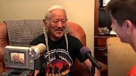 Veteran sitting in chair participates in oral history interview about his service.