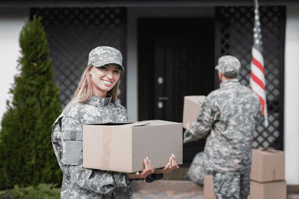 Smiling woman in camouflage holding cardboard box and looking at camera with blurred military man on background