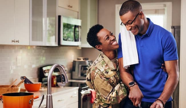 military spouse and husband smiling in the kitchen